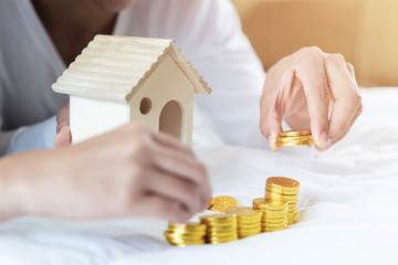 Property ladder, mortgage and real estate concept. Investment and saving concept. Hands making coins stack with house model on bed.