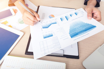 Business and finance concept. Working with analysis paperwork report on table with tablet and mobile, e-commerce or online business technology.