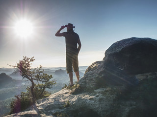 Trekker in cowboy hat on mountain with Sunrise enjoy view