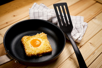Delicious toast with fried egg in pan on wooden kitchen table