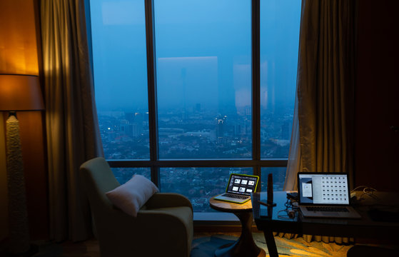 View of megapolis city from inside a hotel room at night. Amazing view through window.