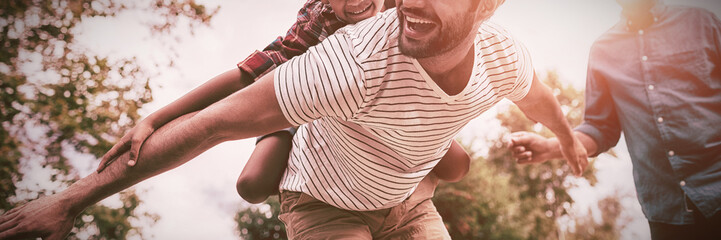 Happy grandfather looking at man giving piggy backing to son