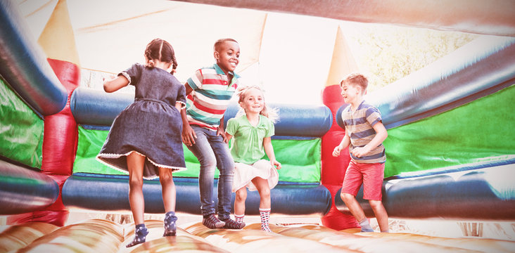 Friends playing on bouncy castle at playground