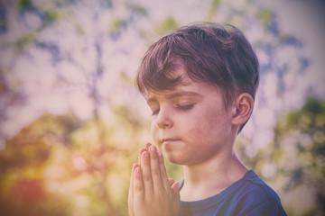 Boy praying with eyes closed