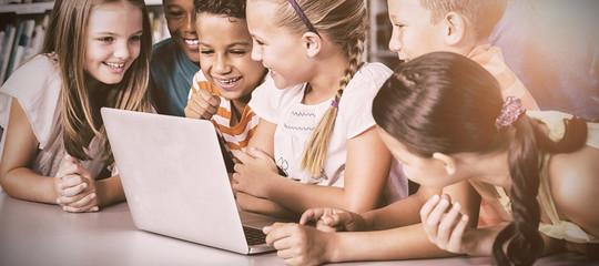 School kids using laptop in library
