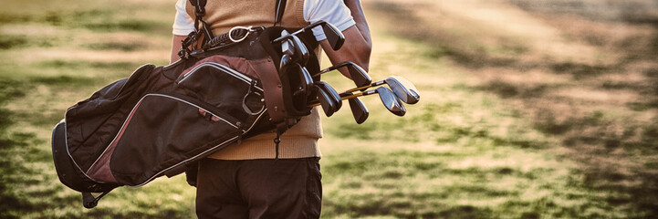 Stores à enrouleur Golf Man carrying golf bag while standing on field