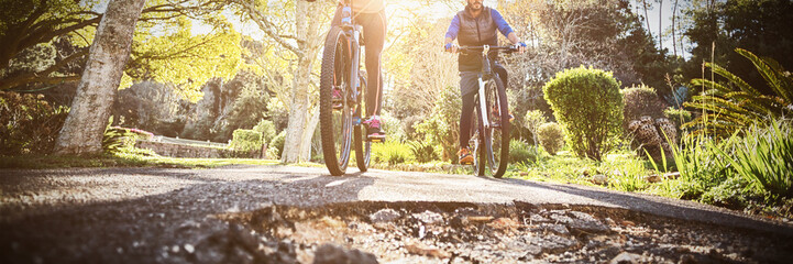Poster de jardin Cyclisme Low angle view of biker couple cycling on countryside road