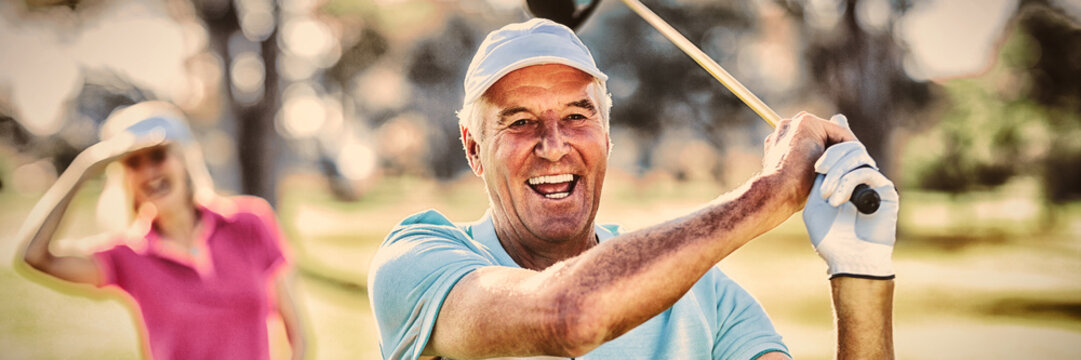 Portrait of mature golfer holding golf club