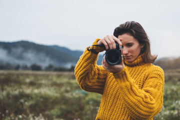 Wall Mural - photographer girl take photo on camera closeup on background autumn mist mountain, tourist shooting nature landscape, hobby concept, mockup copy space