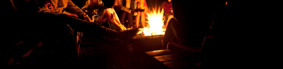 The group of friends are sitting near the bonfire in the night and talking about something