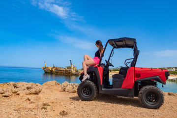 Poster Naufrage Pathos. Island of Cyprus. Woman posing while sitting on a quad bike. Ship wrecked off the coast of Paphos.Woman ATV driver. The beach of Paphos. Mediterranean Sea.A ship crashed near Cyprus. ATV rides