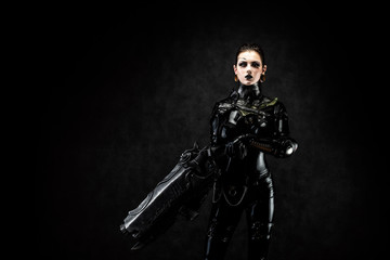 Portrait of a young woman in latex jumpsuit holding a big futuristic weapon in her hands