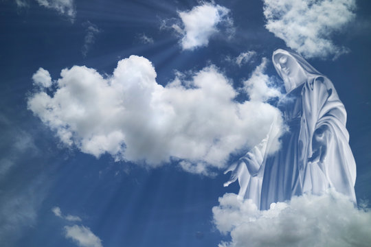 Mary in white clouds with light ray from  heaven.