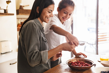 Image of positive family woman and her little daughter cooking together meal with raspberry at cozy apartment