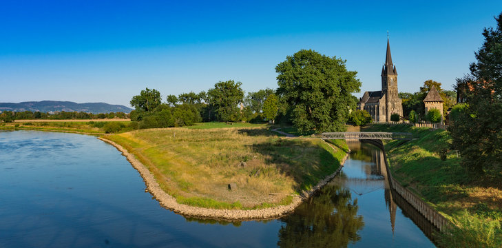 St Sturmius Church and meadow along river Weser. Rinteln, Germany