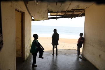 Children play in the remains of a room, gradually destroyed by the storms lashing the coast, in Port Bouet, an area of Abidjan