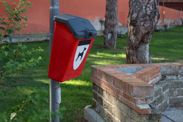 Red plastic bin for dog poo in the park. Concept of clean environment.