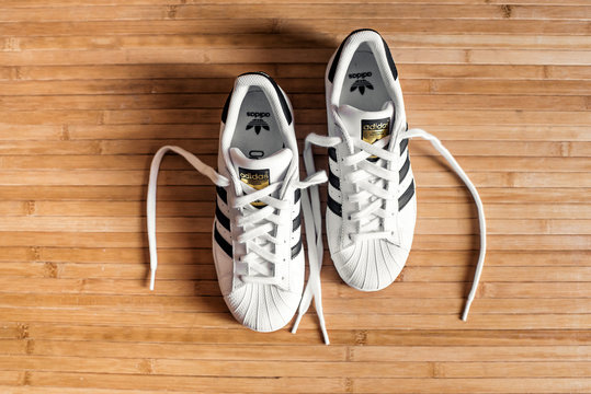 Pair of Adidas Superstar shoes on a wooden floor