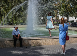 A woman poses for pictures as a man looks on in central Chisinau