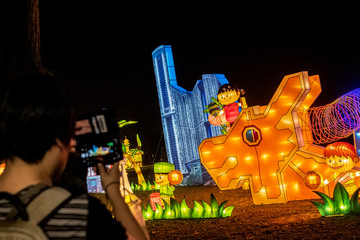 A woman takes pictures of a lantern display depicting Singapore's iconic architecture and multiracial society during Mid-Autumn Festival celebrations at Jurong Lake Gardens in western Singapore