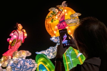 A man takes pictures of a lantern display during Mid-Autumn Festival celebrations at Jurong Lake Gardens in western Singapore