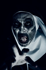 frightening evil nun with bloody teeth