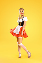 Young sexy Oktoberfest girl waitress, wearing a traditional Bavarian or german dirndl isolated on...