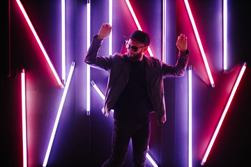 Hipster handsome man on the city streets being illuminated by neon signs. He is wearing leather...