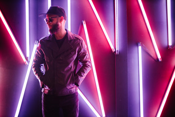 Hipster handsome man on the city streets being illuminated by neon signs. He is wearing leather biker jacket or asymmetric zip jacket with black cap, jeans and sunglasses. Fotomurales