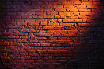 Old retro red brick wall being lit by a stage light bulb light. Constant light modifier projecting light on it