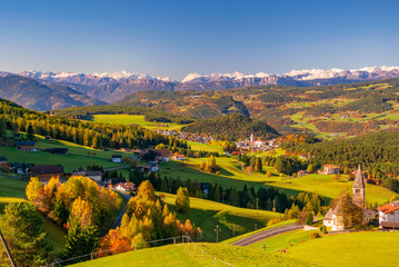 Incredible scenic view of traditional tyrol village with churches in alpine valley at autumn sunny day. Italy