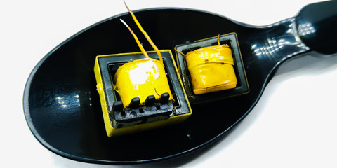 A picture of electric transformers on a black spoon