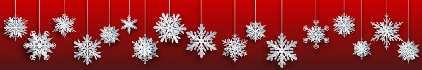 Christmas banner of large white complex paper hanging snowflakes on red background