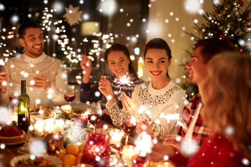 winter holidays and people concept - happy friends with sparklers celebrating christmas at home...