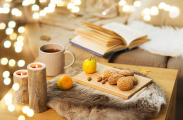 Fototapete - hygge and cozy home concept - oatmeal cookies, lemon tea and candles on wooden table in living room