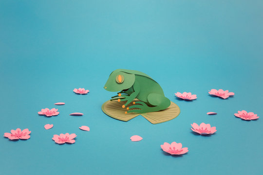 Origami frog on leaf surrounded with paper lilies