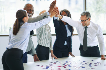 Group of diverse businesspeople laughing and high fiving together while solving a jigsaw puzzle on a table in an office