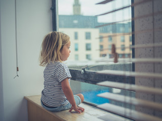 Little toddler sitting by the window of city apartment