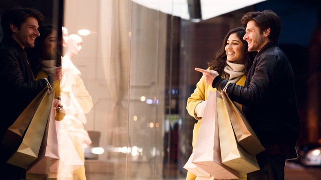Couple looking at fashion store's window, shopping together
