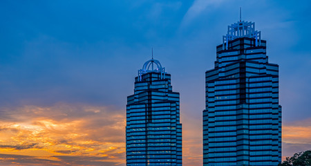 Fototapete - Two blue glass office towers at sunrise