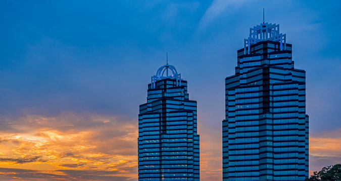 Two blue glass office towers at sunrise