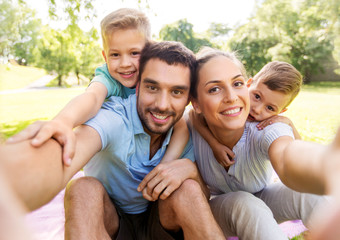 family, leisure and technology concept - happy mother, father and two little sons having picnic and...