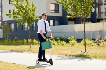 business and people and concept - young businessman with shopping bag riding electric scooter...