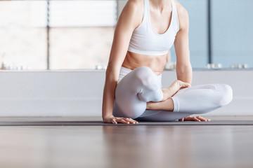 Positive young woman yoga lover doing kukkutasana sitting in white gym. Concept of regular exercise, healthy lifestyle. Arm balance exercise with crossed legs, Scale Posture, Tolasana, Utpluthi Pose
