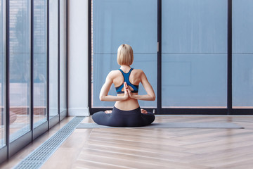 Rear view of a young blonde girl practicing yoga and meditating by joining hands behind her back. Concept of healing body and spirit. Copyspace Blue yoga class, calm and relax, namaste gesture