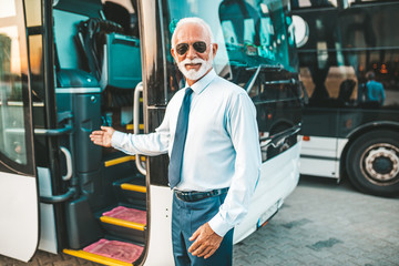 Mature beard bus driver standing in front of bus..