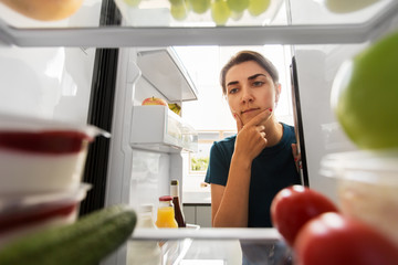 healthy eating, food and diet concept - thoughtful woman at open fridge at home kitchen