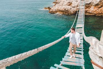 man walking by suspension bridge