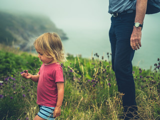 Little toddler walking by the coast with his grandfather
