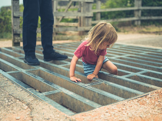 Little toddler playing on a cattle grid